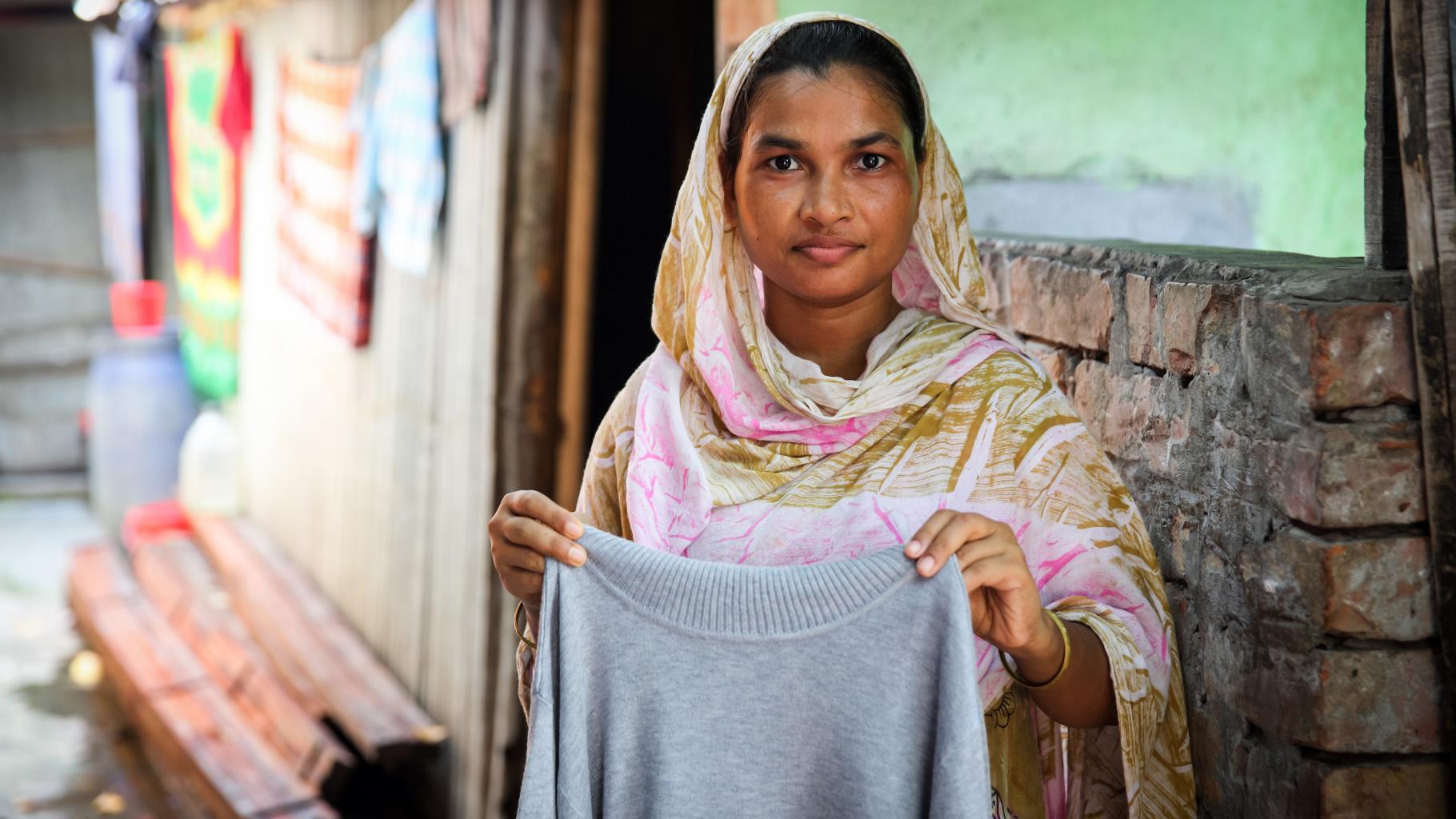 Die Textilarbeiterin Anju hält ein Kleidungsstück, das sie genäht hat.