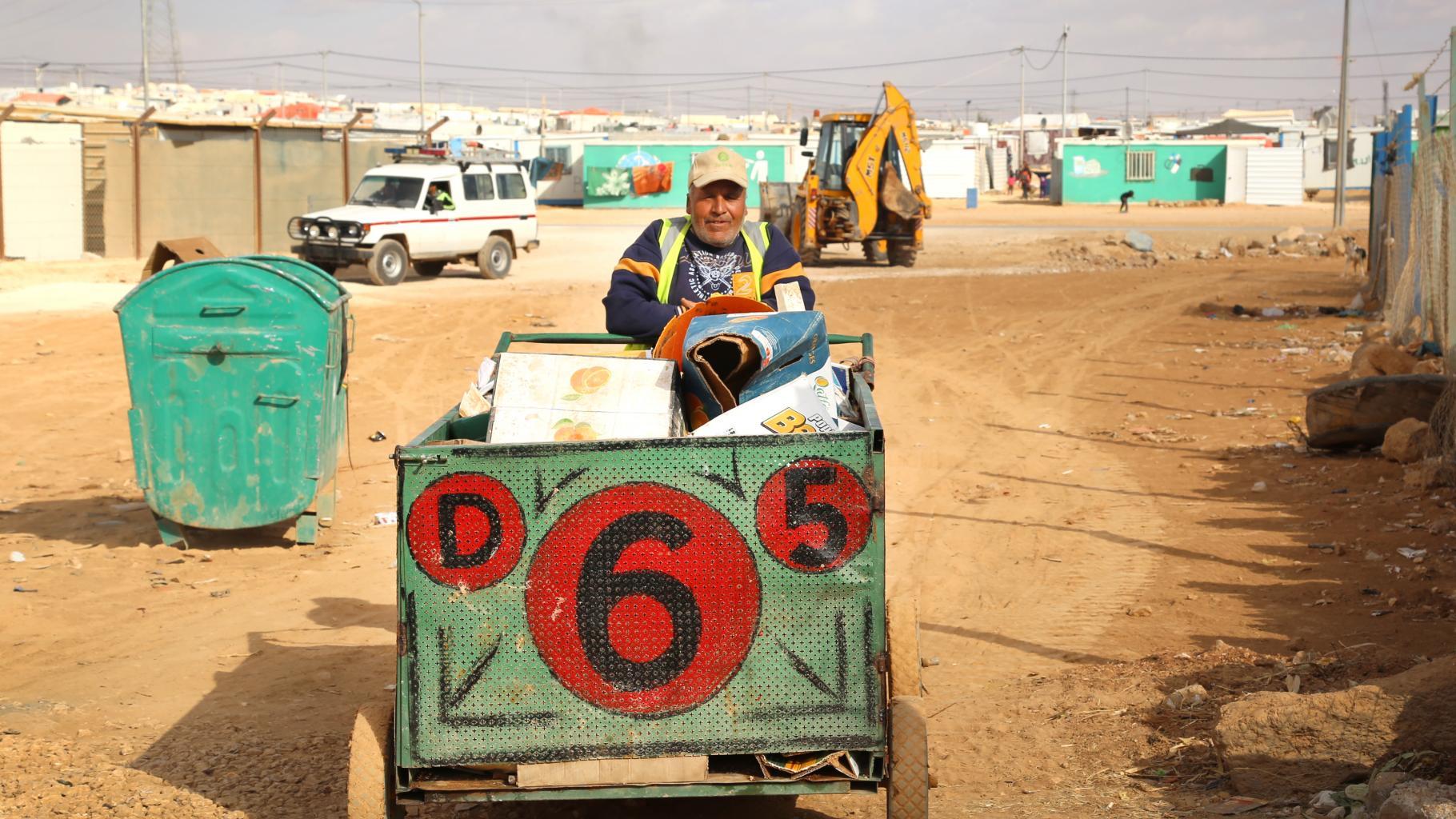 Ein Mann mit Oxfam-Mütze sammelt Abfall in einem Karren.