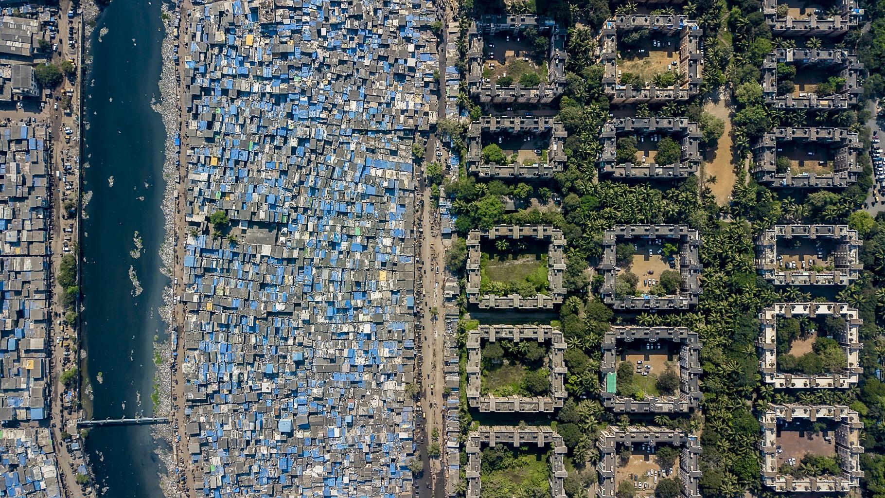Luftbildaufnahme einer Stadt: Einfache Behausungen auf der einen, Wohnungen Wohlhabender auf der anderen Seite