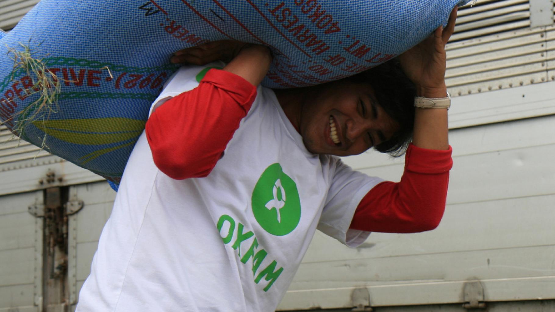 Foto: Ein Oxfam-Mitarbeiter trägt einen Sack Reissamen.