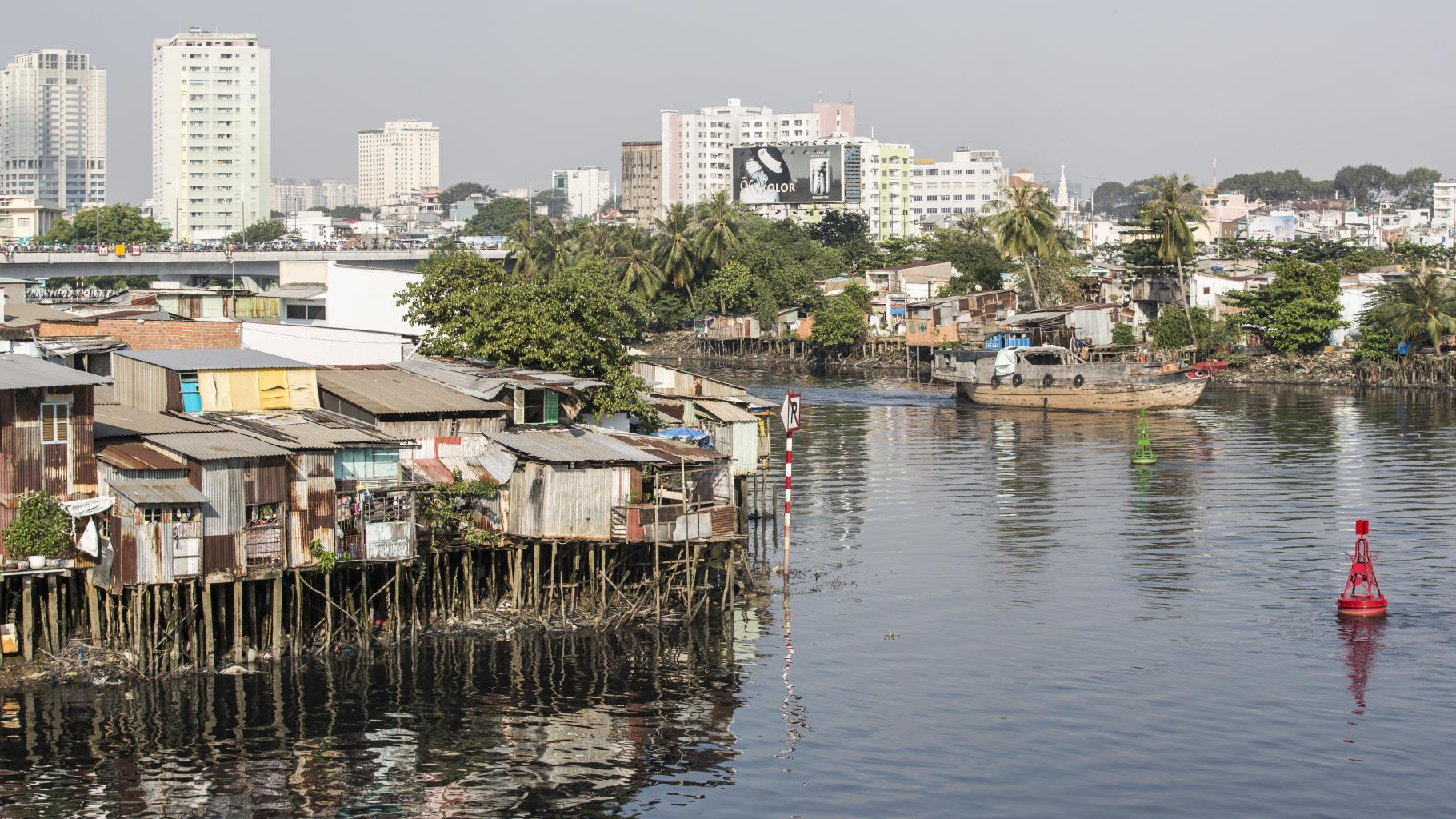 Von einfache Pfahlbauten gesäumt windet sich ein Fluss vor Hochhäusern und einem riesigen Werbeplakat.