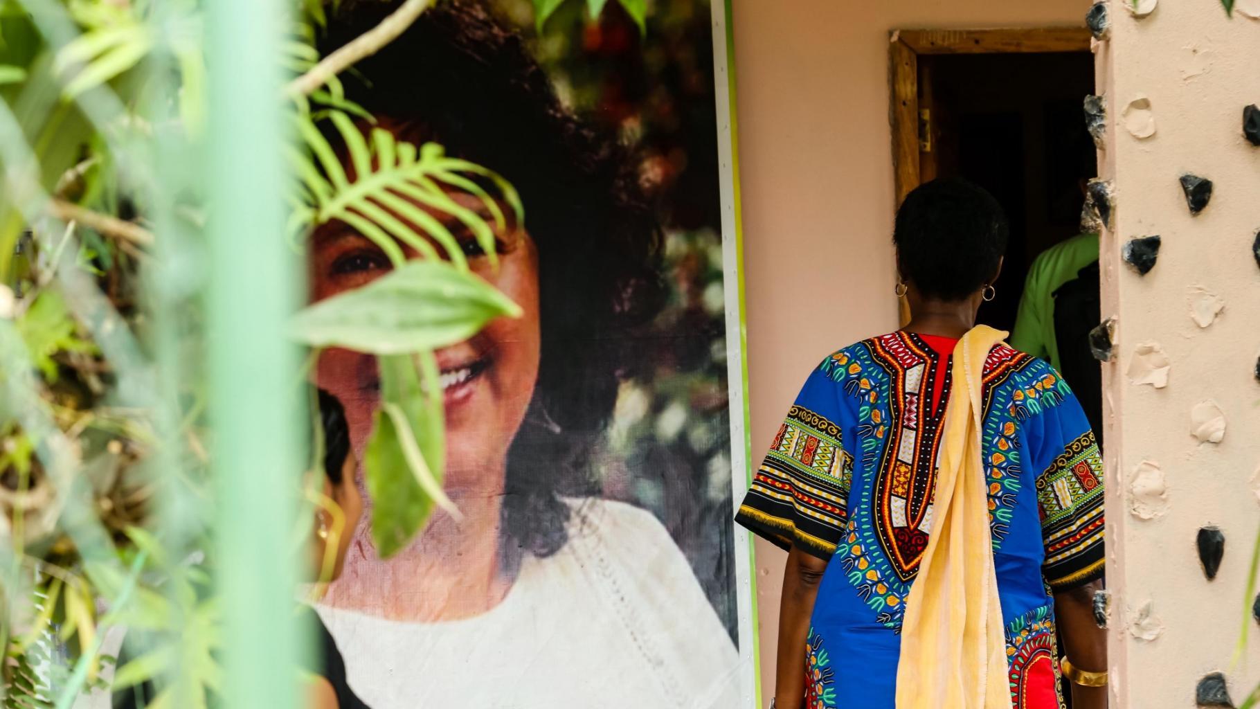 An einem großen Portraifoto von Berta Cáceres im Innenhof vorbei geht Winnie Byanyima ins Haus