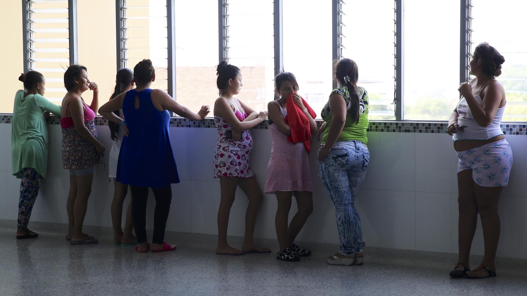 Schwangere Frauen stehen an einem Fenster.