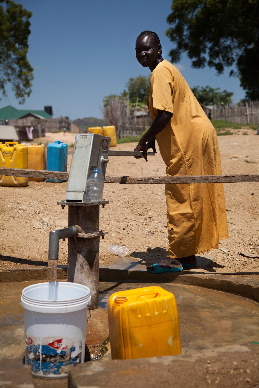 Eine Südsudanesin zapft Wasser.