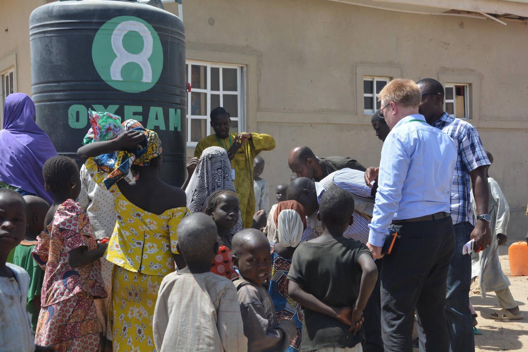 Kinder und Männer stehen um einen Oxfa-Wassertank in einem Camp für Binnenflüchtlinge, Nigeria
