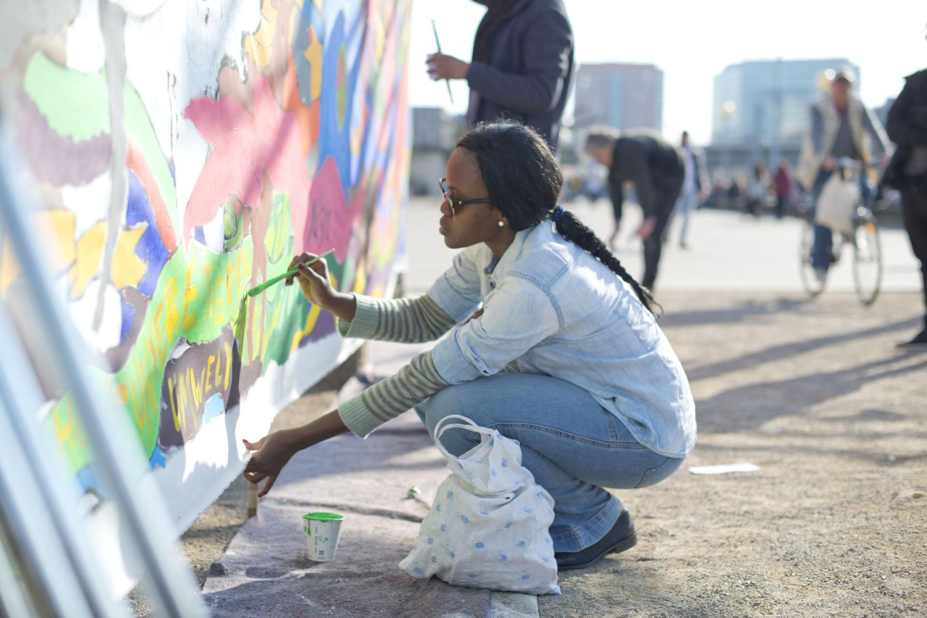 Chinma George bei einer Kunstaktion in Düsseldorf, die auf die Folgen des Klimawandels aufmerksam machen soll.