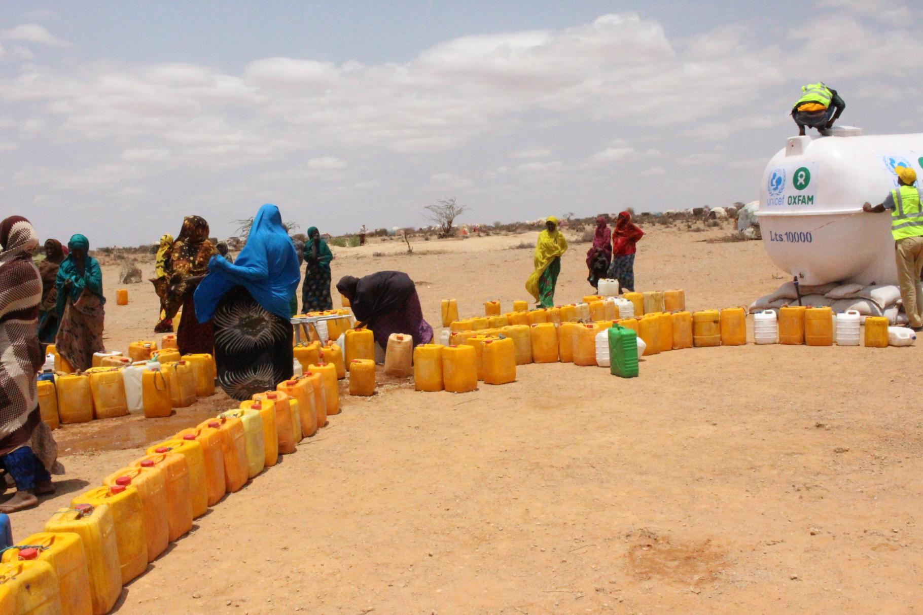 Binnenvertriebene stehen mit Wasserkanistern in einer Schlange im Gunagado-Camp