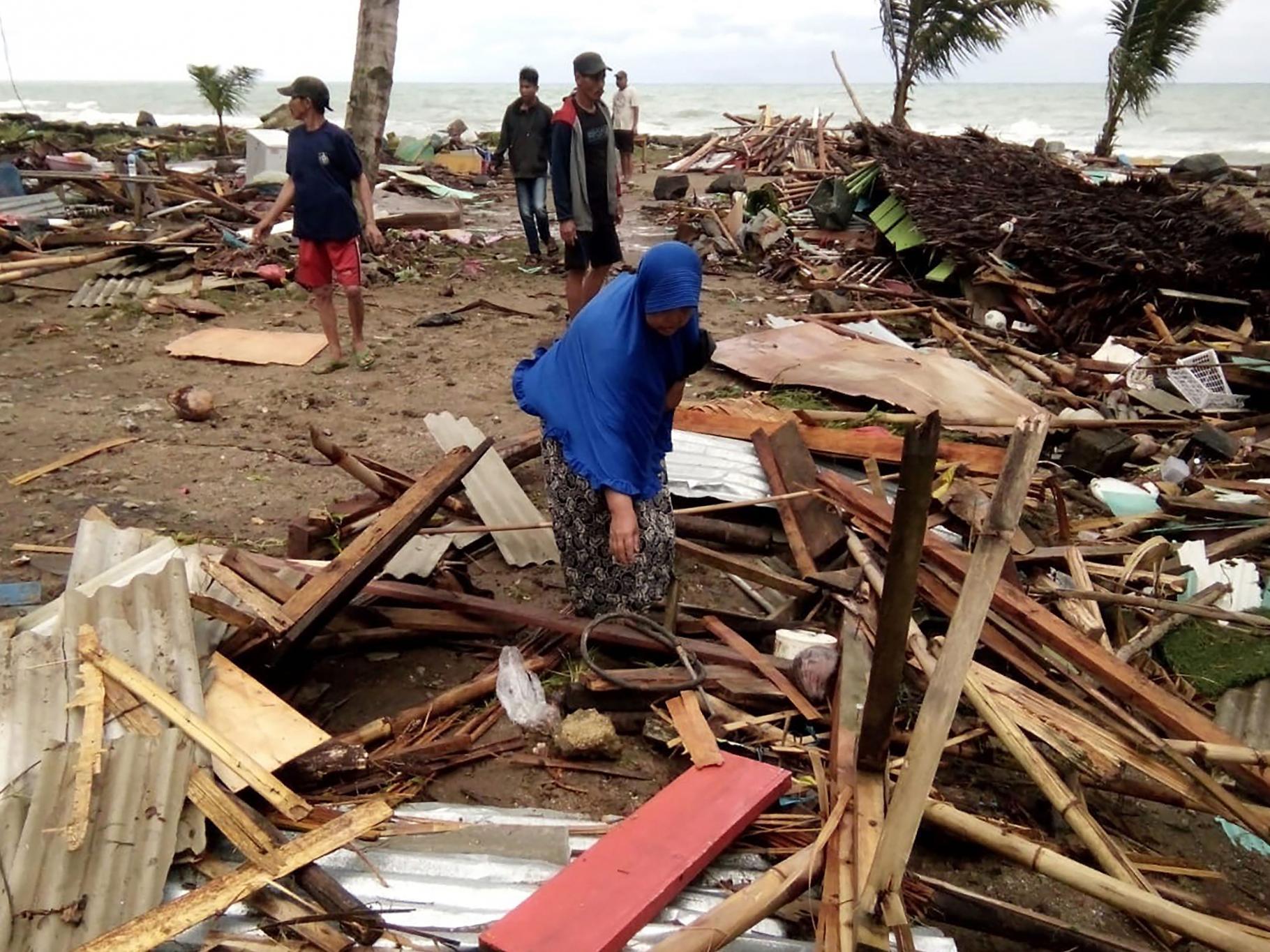 Frau am Carita Beach auf Jawa und das, was von ihrem Haus übrig geblieben ist