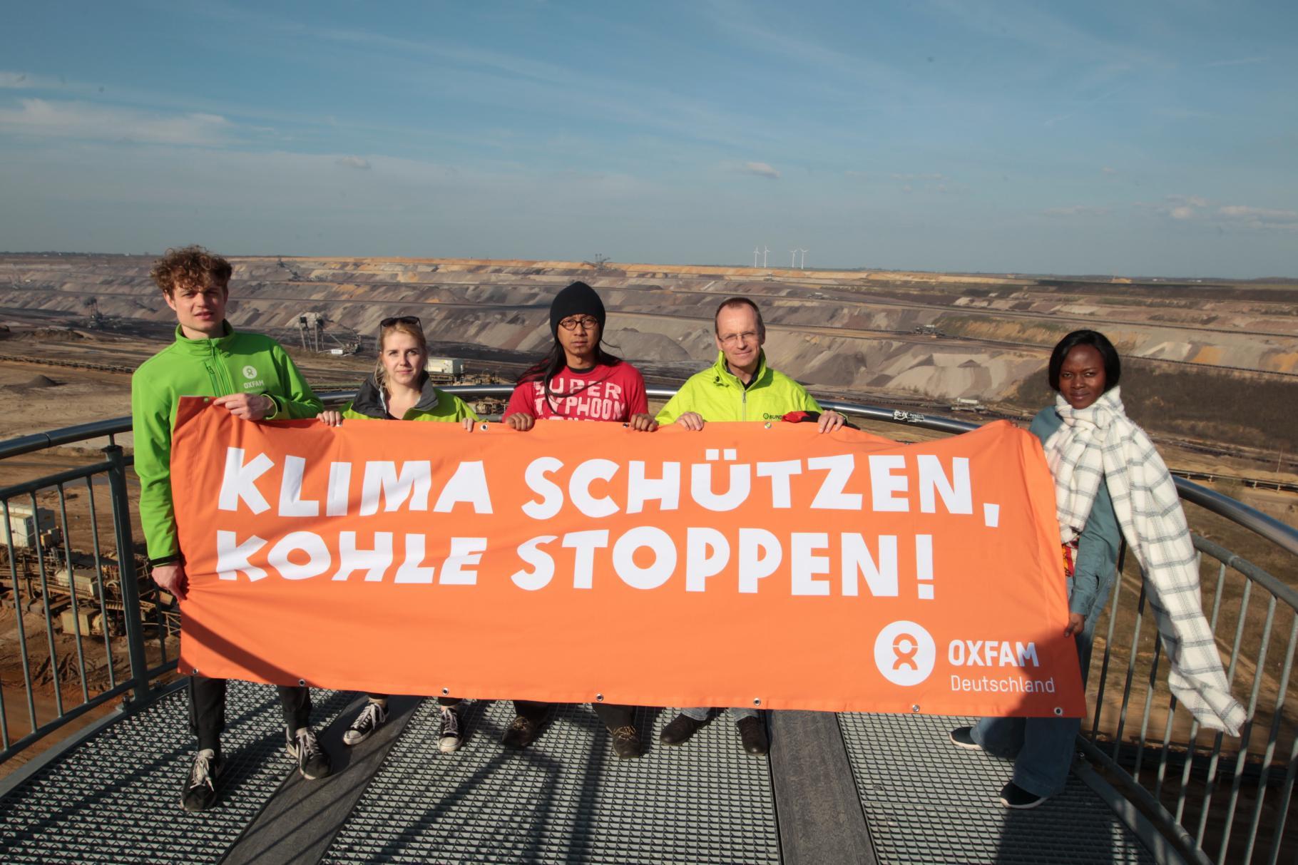 """Klimazeug/innen und Vetreter/innen von Oxfam und BUND fordern mit einem Transparent vor dem Braunkohlebau Garzweiler """"Klima schützen, Kohle stoppen!"""""""