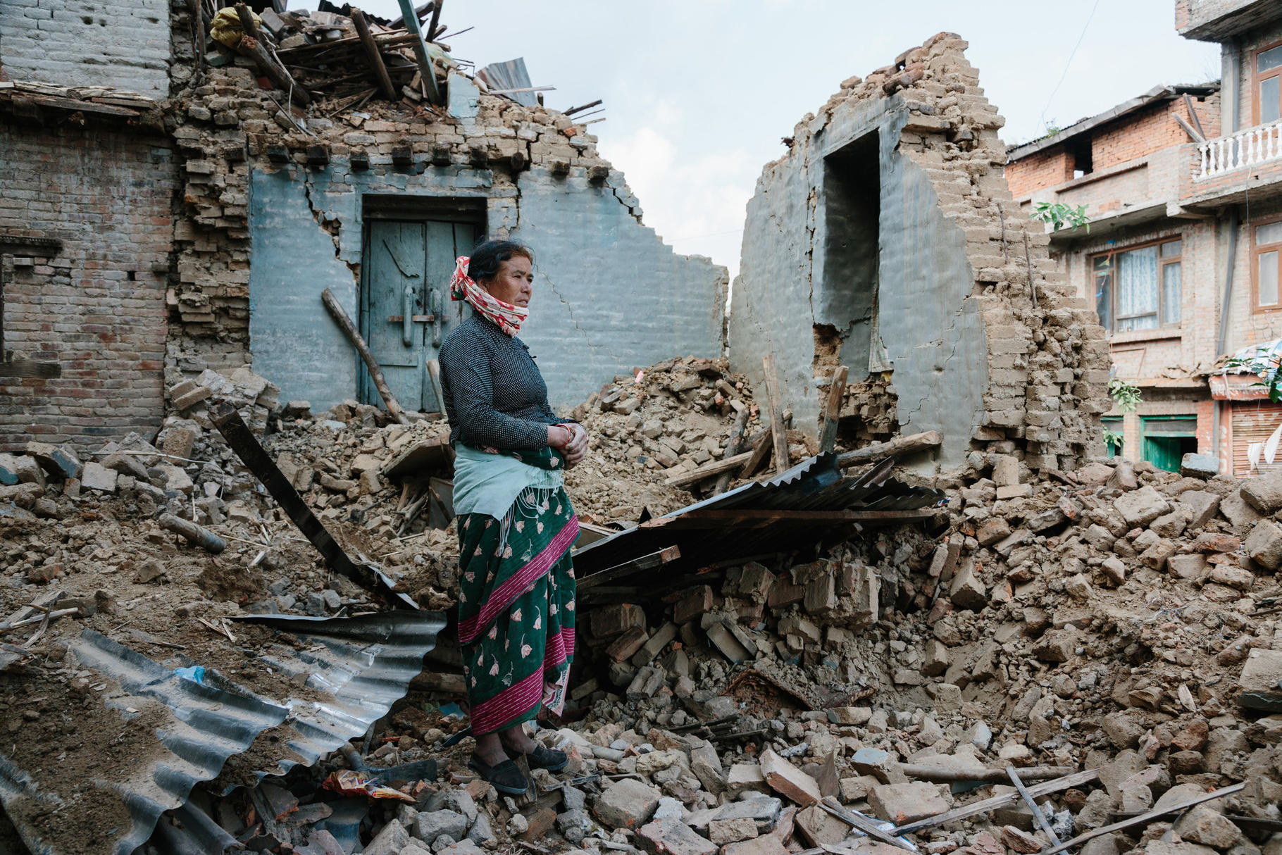 Eine Frau steht vor den Trümmern ihrer Hause in Nepal