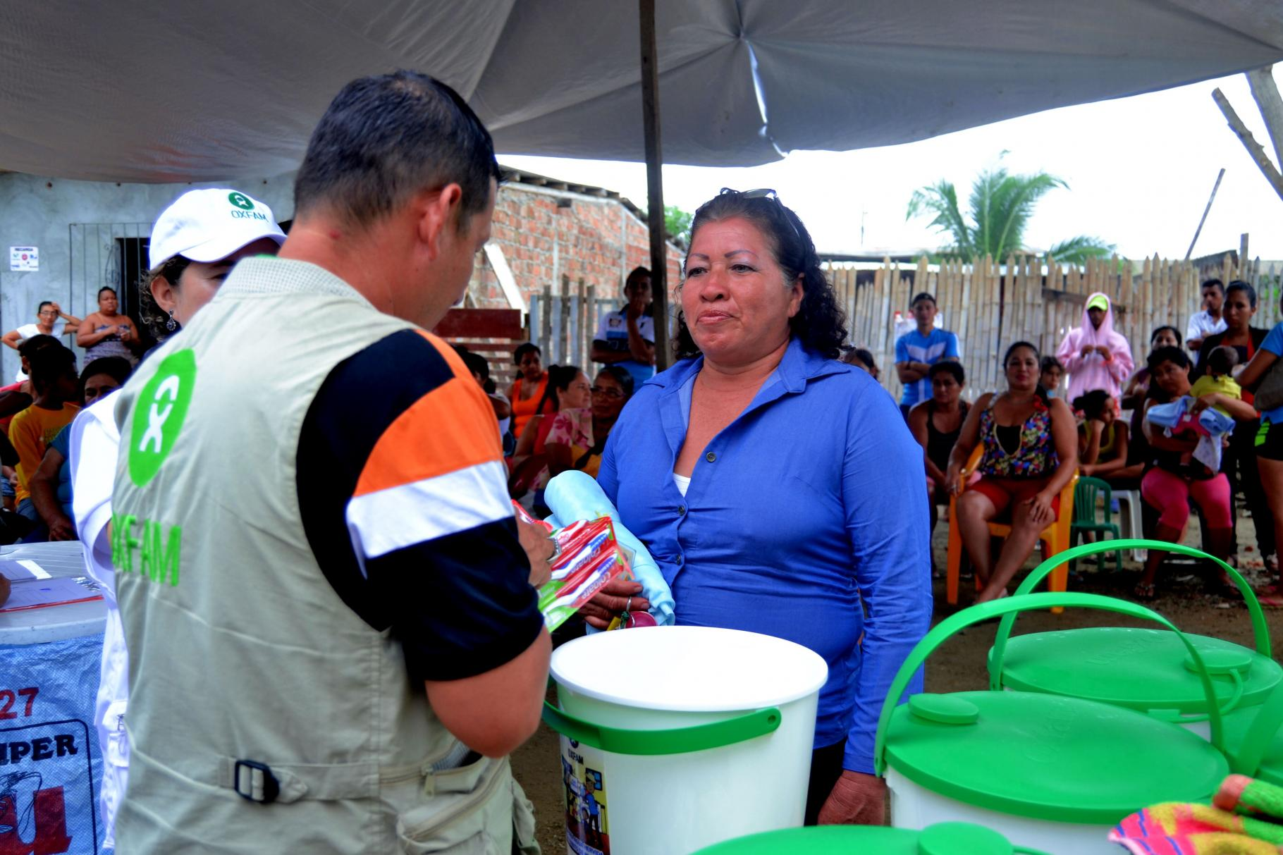 An einer Verteilstation für Wassereimer und Hygiene-Artikel ist ein Oxfam-Mitarbeiter im Gespräch mit einer Frau.