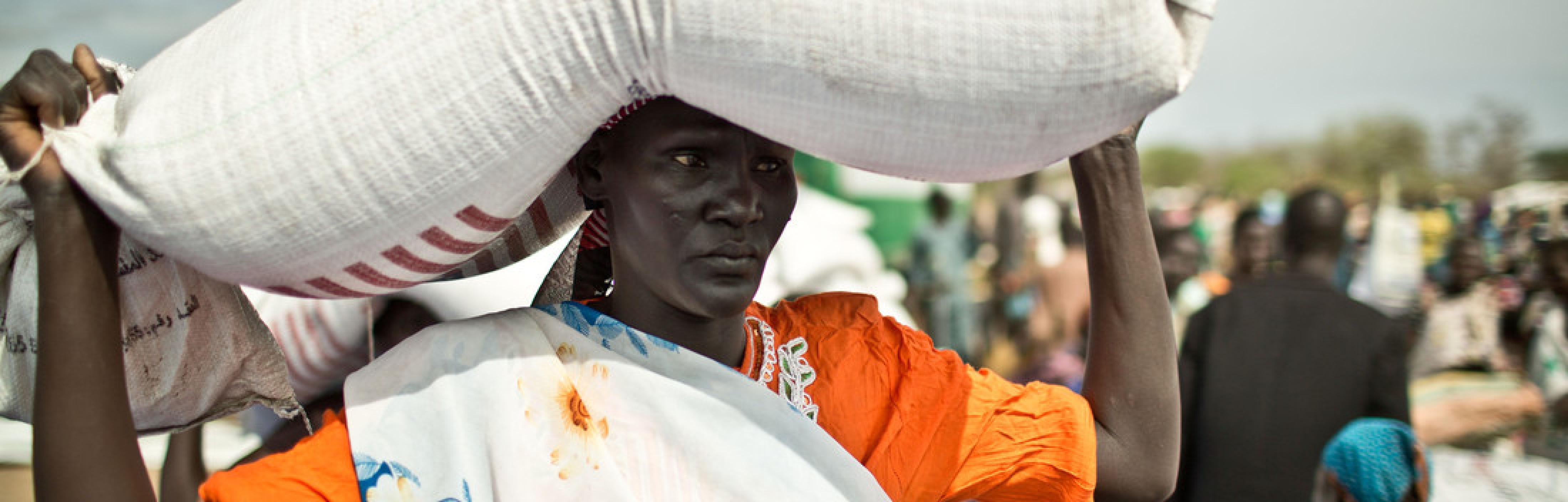 Frau aus dem Südsudan transportiert einen gefüllten Sack auf dem Kopf